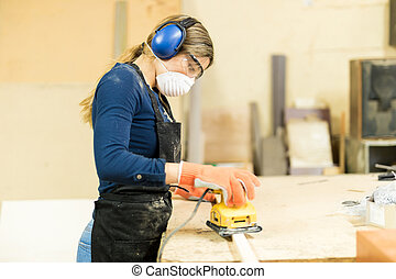Woman sanding some wood in a workshop - Profile view of a...