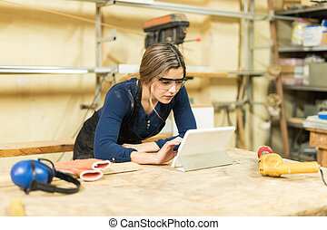Cute carpenter using a tablet computer - Good looking female...