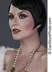 1920s style brunette dancer with short hair and jewelry. She...