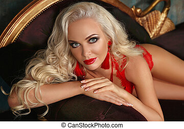 Beautiful fashion smiling woman with red lips makeup and wavy hair style, french manicured nails. Glamour lady posing on sofa.