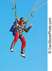 The young parachutist in air operates a parachute