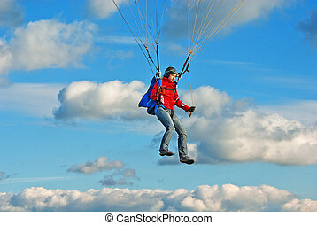 The young girl parachutist in cloudy sky operates a...