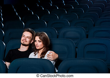 Loving couple watching a movie in the empty cinema