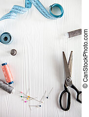 Still life of spools of thread and scissors,  sewing tools and accesories on a white wooden background. Flat lay