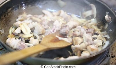 meat with mushrooms fried in a pan - meat with mushrooms and...