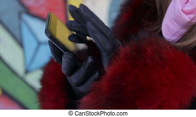 Girl with a tablet in hands outdoors in winter.