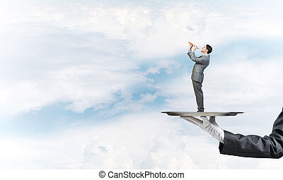 Businessman on metal tray playing fife against blue sky...