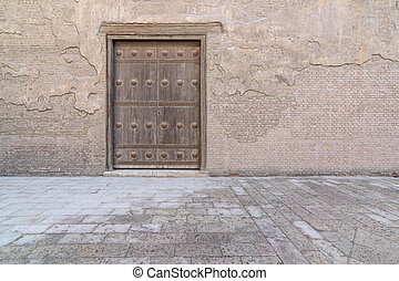Wooden aged vaulted door and stone wall, Medieval Cairo,...