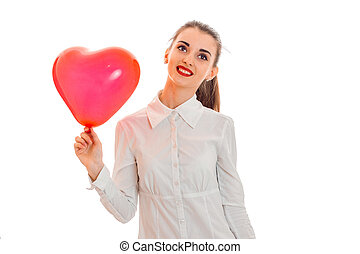 young cute brunette woman in stylish white t-shirt with red heart in her hands looking away and smiling isolated on white background