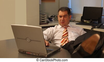 Businessman using laptop in office - Businessman working on...