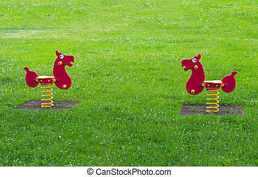 two spring horse toy surrounded by grass in a playground