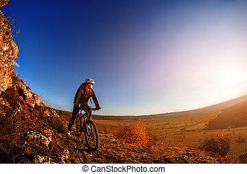 Wide angle view of cyclist standing with mountain bike on trail at sunrise
