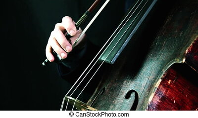 Old cello playing on a black background closeup - retro red...