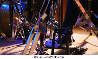 Drummer's foot in sneakers moving drum bass pedal, slider,...