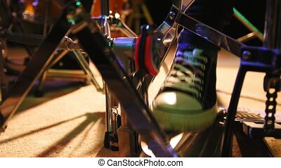 Drummer's foot in sneakers moving drum bass pedal, close up