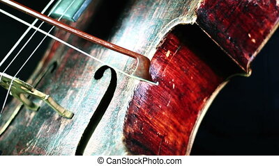 closeup of an old cello orchestral playing - retro red wood...
