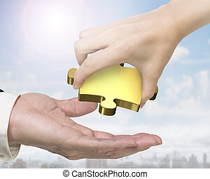 Hand giving one golden puzzle piece - Female hand giving one...