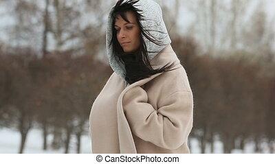 Girl in beige coat straightens, hands combing hair - Young...