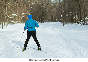 The man on the crosscountry skiing in winter forest. Ice...