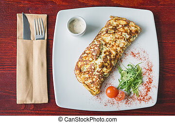 Breakfast omelette with cherry tomato and greens