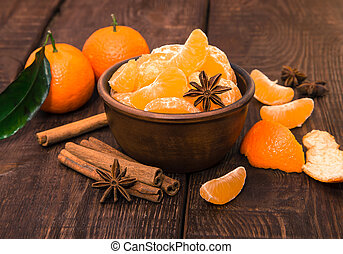 Tangerines with cinnamon stick and anisetree on old wooden...