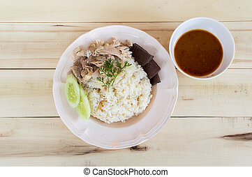Thai food steamed chicken with rice on a wooden table background.