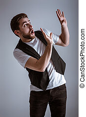 cute young frightened man with beard in shirt and waistcoat...
