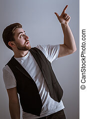 profile portrait of handsome man with beard pointing copy...