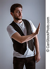 young handsome man with beard in white shirt and black waistcoat shows gesture stop