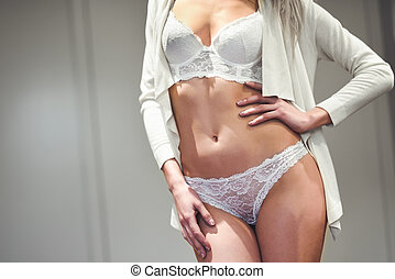 Unrecognizable woman with beautiful body in white lingerie.