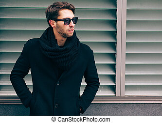 Portrait of young trendy man wearing a black coat with a...