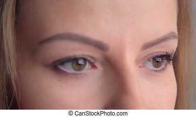 A closeup of a young woman's eyes, she stares into camera,...