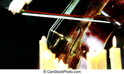 old wooden cello playing in a candles light - camera moving...