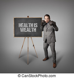 Health is wealth text on blackboard with businessman -...