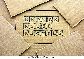 Cardboard card with words Reduce Reuse Recycle made by black...