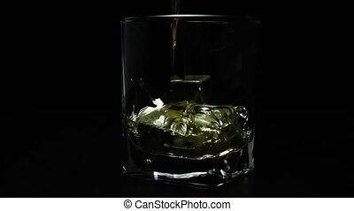 Whiskey poured into a glass super slow mo