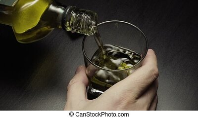Male hand pours whiskey from a bottle and takes a sip