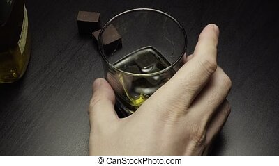 Male hand turns glass of whiskey and takes a sip