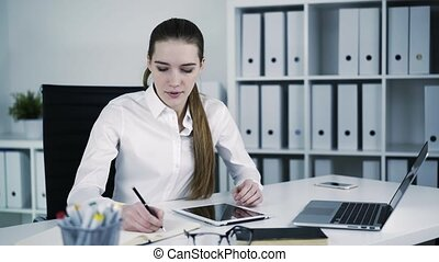 Businesswoman working and making some notes in front of computer in office.