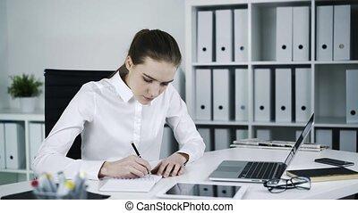 Sad woman at workplace making notes. - Sad woman at...