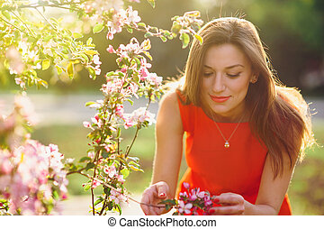 beautiful young woman smelling a flower in the spring park