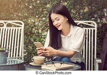 happy smiling asian woman using technology on her computer...