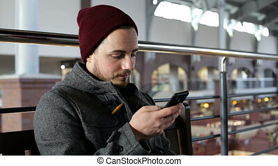 Portrait of young happy man with smartphone sitting in big shop