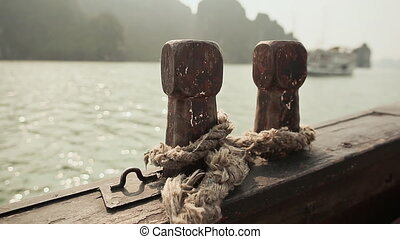 Two wooden bollards with an old rope on a moving ship at sea