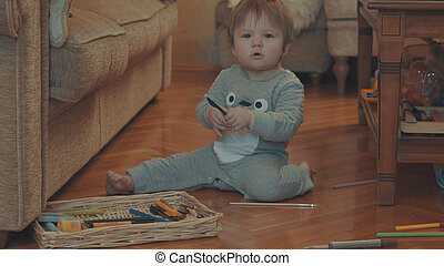 Little baby playing on the floor with a plastic knife. Eye...
