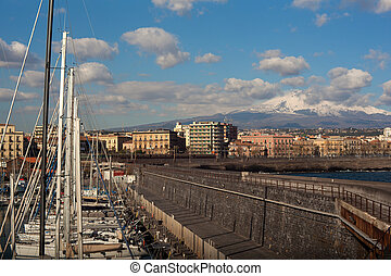 View of Catania from harbor, Etna volcano on background,...