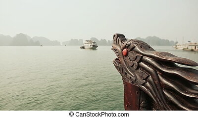 A boat with a dragon's head floating in the ocean. Vietnam. Ha Long Bay.