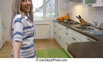 Lovers enjoying their new house enter the kitchen holding...