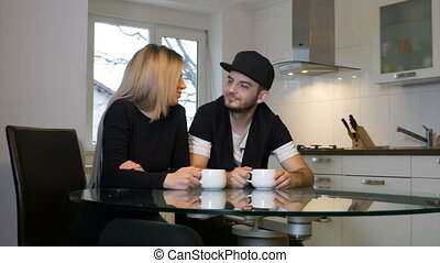 In love couple having coffee and kissing at home in the...