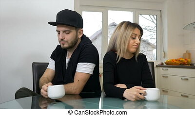 Upset sad couple drinking coffee after a fight sitting in...